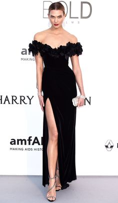 KARLIE KLOSS in a body-hugging black Marchesa gown with a rosette-adorned off-the-shoulder necklace, delicate dangling earrings and equally sparkling cuffs (all Chopard) and Giuseppe Zanotti Design shoes.