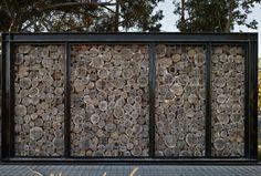 Dieser Gabionenzaun besteht aus einem Metallrahmen und Holzscheiben