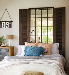 Dormitorio con cabecero de espejo en forma de ventana
