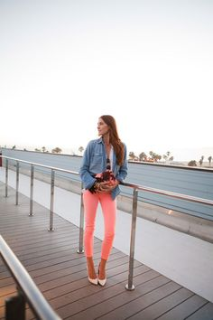 """""""What's better than a hot summer night? Hot neon pants. I've been living in these skinny, cropped jeans from J.Crew and especially love them paired with my Dezso palms pouch."""""""