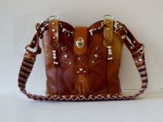 This SSC bag is named Wild Flower.  Her vintage cowboy boot leather is mottled colors of prairie tan.  She is one of a kind, handcrafted, and numbered.  Great bag for summer vacations.  www.stagecoachbagsandcollectibles.com Summer Vacations, Cowboy Boots, Purses, Flower, Colors, Leather, Bags, Vintage, Handbags