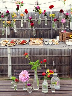 Simple glass bottles and flower display. Perfect decor for a garden party!