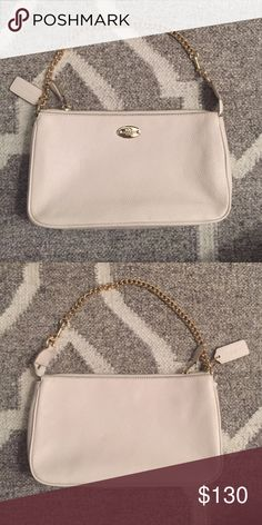 *New* Coach Cream Pebble Leather Handbag/Wristlet Brand new (with tag) incredibly soft leather with a plump pebbled texture gives the refined handbag/wristlet a luxe feel. The polished gold chain converts it from wristlet to top handle purse. Inside cream fabric lining with credit card and multifunctional pocket. 9 1/2'' (L) x 5 1/2'' (h) x 2'' (w). Coach Bags Clutches & Wristlets