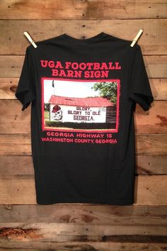 UGA Football Barn Sign Shirt available in long and short sleeve pocket tees. Support the Bulldogs with this licensed tee available in three colors: Red, Black & Granite!