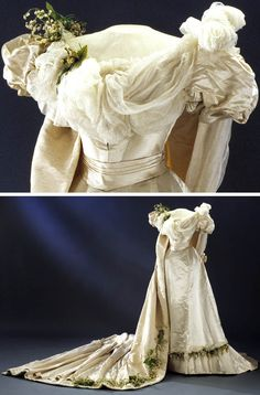 Wedding dress, probably Swedish, 1897. Ivory atlas with white silk taffeta over bust and satin ribbon at waist. Yellow & white orange blossom and lily of the valley in wax & fabric attached to shoulder, hem, & train. Train of ivory silk rep (possibly moiré) lined with off-white, very dense silk twill. Padded hem.