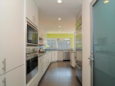 A green accent wall draws the window at the far end of this sleek galley…