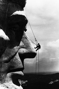 A repairman glides down the face of Abraham Lincoln at Mount Rushmore, 1962