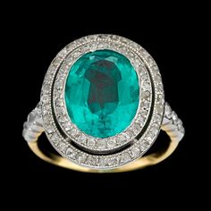 A Colombian emerald, diamond and platinum-topped eighteen karat gold ring  circa 1910  centering an oval-cut emerald weighing approximately: 3.15 carats; in an old single-cut diamond double surround; total diamond weight approximately: 0.65 carat.