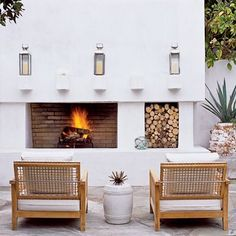 I love firewood stacks...A simple outdoor fireplace makes a patio or porch functional year-round. Plush cushions on comfy wide-backed chairs make it the perfect place for enjoying a cocktail on a cool evening.
