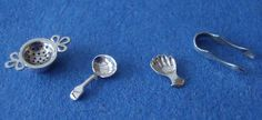 Mike Sparrow: Tea Strainer (left) pierced handles and bowl, sits on a separate drip pan Caddy Spoon (centre left) fiddle pattern,  Caddy Spoon (centre right) kept in caddy and made in many shapes and styles, this one being in the form of a hand Sugar Tongs (right) 9mm long.