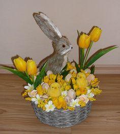 jarní košík se zajíčkem Větší jarní nebo i velikonoční dekorace v proutěném šedém košíku průměru 24 cm, plný jarních kvítků v bílé a žluté barvě,uprostřed sedí slámový zajíček. Výška dekorace 34 cm.