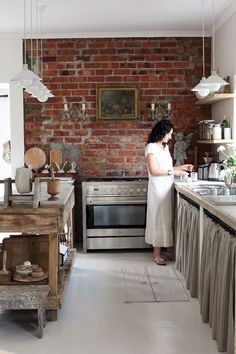 Love this kitchen with the exposed brick, wall sconces, curtained storage and rustic timber island bench