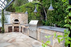 This stunning, state of the art outdoor kitchen boasts a gorgeous natural tiled cabinets that lead to a gorgeous wood burning oven. Lush greenery and hanging ivy provide a phenomenal natural backdrop.