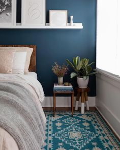 Navy walls and teal rug in moody bedroom decor