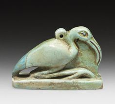 An Egyptian bichrome glazed composition amulet of an Ibis of Thoth  Late Dynastic Period, circa 664-332 B.C. Depicted squatting, in turquoise glaze, with long curving beak and suspension loop behind the head, the eyes and tail in darker turquoise glaze, 1 5/8in (4.2cm) long