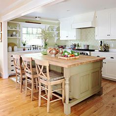 Green on the island and backsplashes pairs with white cabinetry to communicate classic appeal in this kitchen. Beaded panels give the island cottage charm, while a glossy finish on the subway tiles updates the look. The island's butcher-block top lends warmth to the abundance of white and provides a practical surface for meal prep./