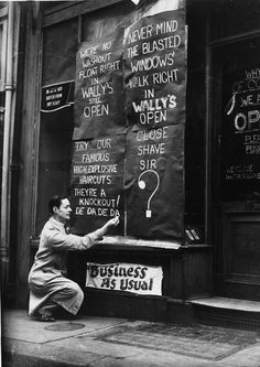 21st November 1940: Wally's barber shop, St Martin Street has defiant signs outside after losing its windows during the London blitz.