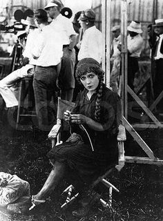 ca. 1920 --- Silent film star Mary Pickford (1893-1979) won an Academy Award for her performance in in 1929. She was cofounder in 1920 of United Artists Films with D.W. Griffith, Charlie Chaplin, and Douglas Fairbanks, her second husband. Here she knits as she waits on a film set. --- Image by ? CORBIS