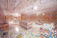 """The Japanese artist Yayoi Kusama transformed a completely white room, including furniture, into a spectacle featuring her signature dots, helped by children who visited the exhibition over two weeks and placed brightly colored stickers throughout the installation at the Gallery of Modern Art, Brisbane."""