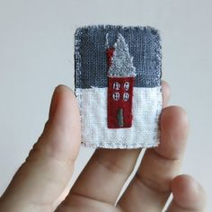 This sweet brooch has a cozy little red cabin in the snow hand embroidered with linen and cotton fabrics and has a dark grey wool felt backing. Size: About 1 1/4 inches wide by 2 inches tall I do my best to get the colors as true to life as possible but please keep in mind that the colors may vary from monitor to monitor. You can find more of my brooches here: http://www.etsy.com/shop/Sidereal?section_id=7924086 or Click here to go back to my shop home page:...