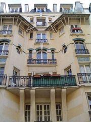 Immeuble d'habitation (1902) 21, rue du Simplon Paris 75018. Architecte Henri Sauvage. La terrasse du troisième étage est l'occasion d'un jeu de toitures et de garde-corps assez riche, tandis que la charpente en bois qui déborde largement au 5ème étage donne un petit air normand. Les touches de couleur apportées par les céramiques placées dans les allèges et les briques vernissées vertes des linteaux, dynamisent la façade en brique.