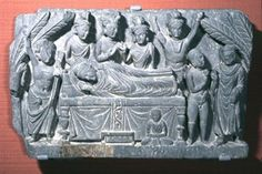 Panel showing the Death of the Buddha. Lying on his side, head turned to his right and feet away from each other, the Buddha holds his right hand, apparently emerging from the high neckline, as if in abhaya below his head and against the bordered halo. His left hand is covered by the robe, which continues in pleats below it. The hair is wavy into the uṣṇīṣa, the long oval