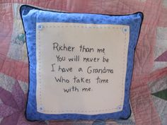 "This 14"" square pillow is hand-embroidered in black floss with a sweet message about Grandma. It is trimmed in blue calico and outlined in piping."