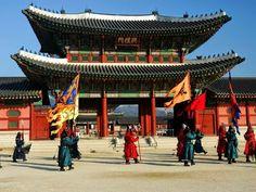 """Palácio Gyeongbokgung, Seul  Foto de Anthony Plummer  Os guardas do Palácio Gyeongbokgung fazem a troca da guarda com  freqüência, como tem sido desde 1395, quando um palácio foi construído neste local no centro de Seul durante a Dinastia Joseon. O """"palácio muito abençoado pelo céu"""" foi destruído pelos japoneses no final do século 16 e, novamente, durante a Segunda Guerra Mundial. Ao longo das últimas duas décadas os coreanos foram restaurando Gyeongbokgung e devolvendo a sua antiga…"""