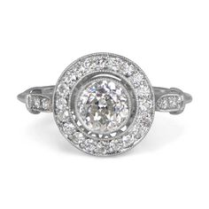 The Brighton Ring is a beautiful halo engagement ring, sporting a beautiful old mine cut diamond that is bezel set in a handcrafted platinum mounting. The triple wire shank and the diamonds along the shoulders adds to the delicacy of the ring.The center antique diamond was cut circa 1915 and weighs approximately 1.25 carats, J color and VS2 clarity.