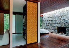 A lareira do quarto rústico fica incrustada na parede de pedra