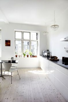 White kitchen- white washed wooden floorboards, kitchen chairs, black work top