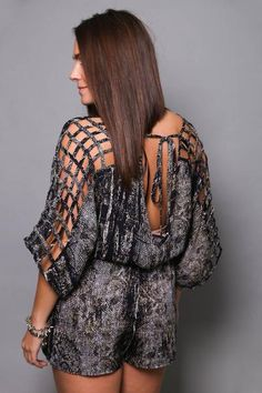 Polyester. Navy + Cream snakeskin detail. Ladder cut outs along shoulder-line with an open back. This romper is so fierce and fun! Model in this photo is a 4/5