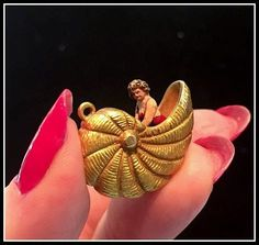 antique gold charm featuring a bathing beauty in a shell