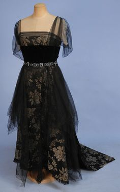 SILK and LAME EVENING DRESS, c.1918. Black satin with gold lame roses, bodice having square neckline with black net sleeve over cream chiffon, black velvet midriff band decorated at the waist, back and shoulder with jet, steel and crystal beads, net over-skirt and asymmetrical train. New York label. B-36, W-28. $200-300. - my note: massive error in the dating, should be 1918 instead.