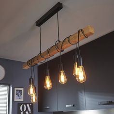 Suspension équipée de 6 lumières de la collection Townshend, composée d'une rosace de plafond rectangulaire et d'un bras tubulaire en bois naturel distribuant six cordons d'alimentation de couleur...