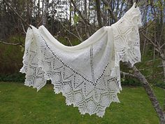 A shallow triangular shaped shawl with a border of knitted lace, and the main body of stocking stitch.