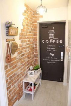 decoration couloir long et etroit, mur en briques rouges, sol en parquet gris finition lisse, porte en marron avec inscription Caffé, petit banc blanc avec étagère pour les chaussures, patère en bois clair, luminaire en style art déco