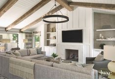 Reclaimed Wood Vaulted Ceiling Living Room with TV Over Fireplace and Neutral Couch #livingroomdesignswithtv