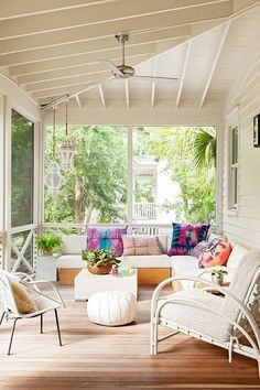Screened in deck cooled by a ceiling fan hung over a wood plank floor features a…