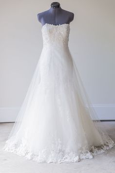 Enzoani - Size 4 - This stunning Enzoani gown features tulle and lace overlaying a satin silhouette, with peekaboo lace detailing, an exquisitely beaded bodice, and a dramatic lace edged tulle train.