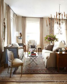 hanging draperies - Slim taupe pleated drapery panels hanging from rods bolted to the ceiling - ElleDecor via Atticmag