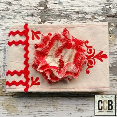 Hello! Charity here from Scrappin' Chaos with a beaded rose ornament to glamorize your tree. This red tipped flower takes about 30 minutes to put together including the drying time. The secret is to begin with a burlap flower from Canvas Corp Brands. I used an ivory colored flower, but Canvas Corp has many colors of pre-made burlap flowers. Stop by the CCB Shop and view them all! Supplies: (Canvas Home Basics) Burlap Flower, Ivory (Tattered Angels) High Impact Paint, Red Thread Beads ...