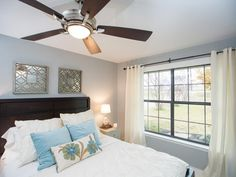 Pale blue accents, soft window treatments, classic wood headboard and stylized fan bring casual comfort and elegance to the new bedroom.