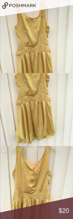 Yellow Satin Circle Ruffle Dress Adorable yellow dress made of a satin- like polyester material. Dress is fully lined, has zipper, and functioning buttons in the back. Includes pockets and drop waist with a full ruffle circle skirt. No brand but fits L. Good condition other than two small stains in front of skirt. Dresses Midi