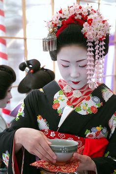 Katsuryu, a young maiko who recently made her debut in Kamishichiken, prepares to serve matcha, whisked, powdered green tea, to guests at Kitano Tenmangu Shrine, in Kyoto, Japan