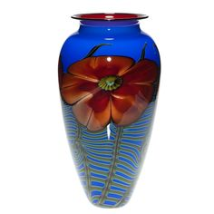 Humler & Nolan | November 2013   Large vase, the creation of Richard Satava featuring homogenous red peachy blossoms backed by fronds of ferns against a royal blue backdrop. Scarlet red cases the interiorand a black lip wrap finishes the rim.