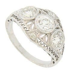 A trio of brilliant round cut diamonds are bezel set into the face of this antique platinum engagement ring. Elegant organic cutwork surround the dazzling stones, while an additional quartet of fine faceted diamonds are set above and beside the center stones. Zig zag filigree frames the center design, while organic engraving covers the sides and shoulders of this phenomenal ring. The Art Deco ring holds a total weight of 1.70 carats of round cut diamonds and measures 12.24 mm in width…