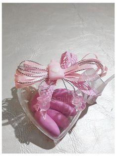 Bomboniera composta da una scatolina a forma di cuore in plexiglass riutilizzabile come portaoggetti chiusa in cima con un applicazione in resina trasparente a forma di ciuccio su gioco di nastri in raso rosa, chiusi nella scatolina 5 confetti al cioccolato Maxtris colore rosa.