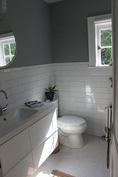 A look at the bathroom's refurbished square window, subway and penny tiles, and walls painted in a slate gray by Benjamin Moore
