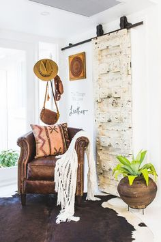 Nook with a leather armchair, a rolling door, and a cowhide rug